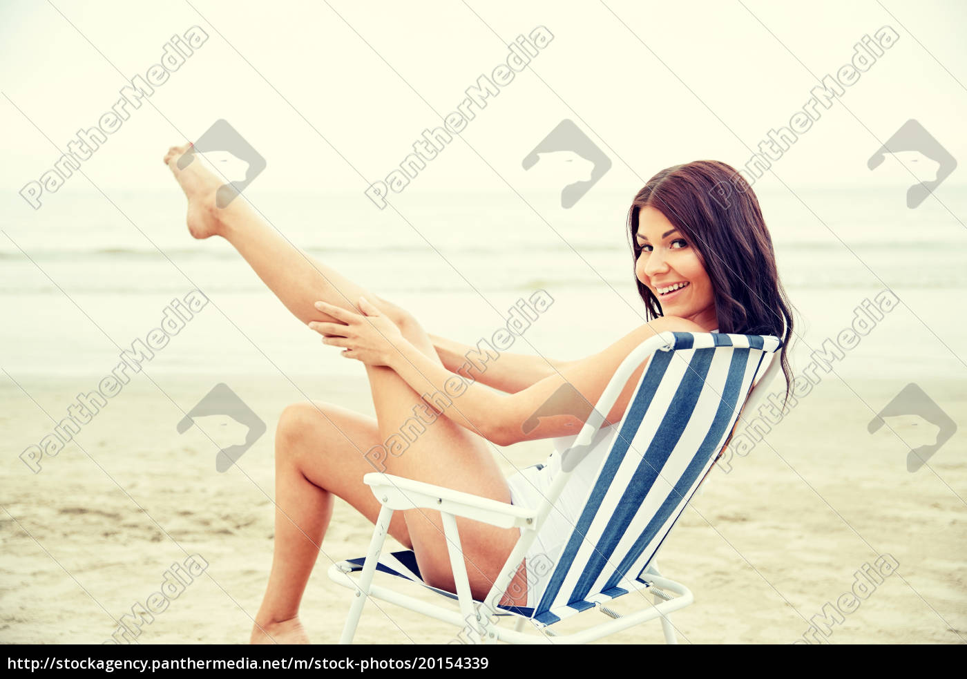smiling, young, woman, sunbathing, in, lounge - 20154339