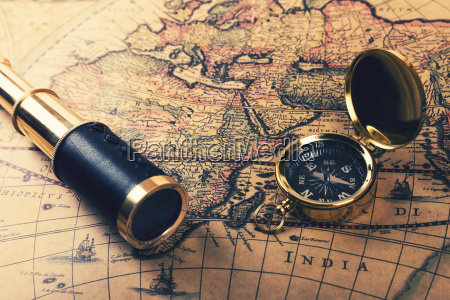 vintage compass and spyglass on old