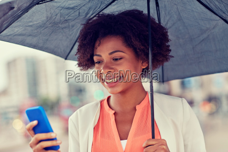 businesswoman, with, umbrella, texting, on, smartphone - 20169635