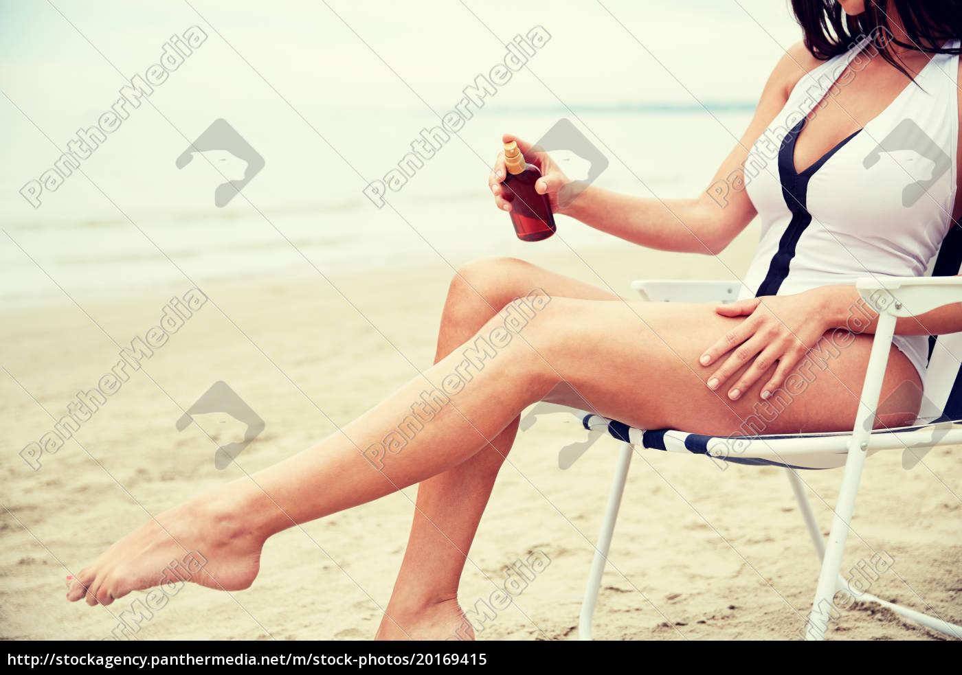 woman, sunbathing, and, spraying, sunscreen, on - 20169415