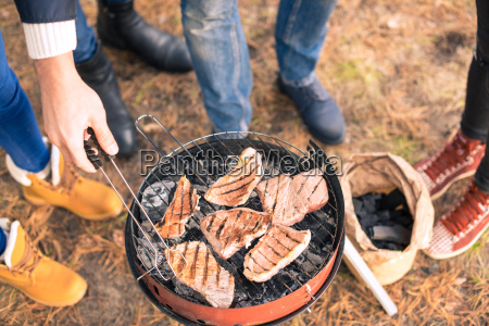 people cooking meat on charcoal grill