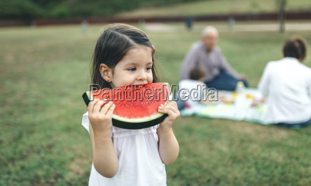 girl eating watermelon slice with her