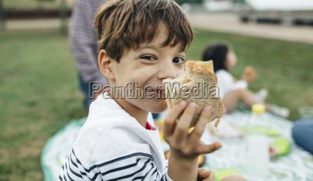 portrait of smiling boy holding sandwich