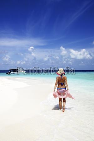 maldives woman walking on sand beach
