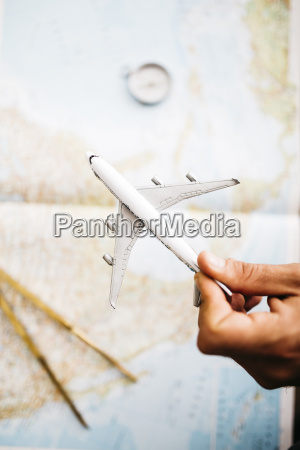 hand holding airplane model in front