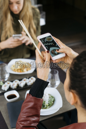 woman taking picture of sushi in