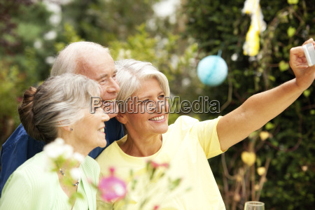 senior man taking selfie with guests