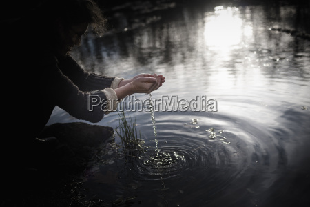 woman crouching at waters edge scooping