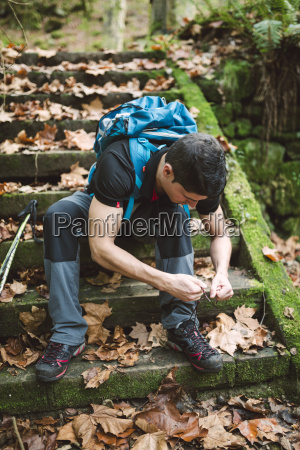 hiker sitting on stairs lacing his