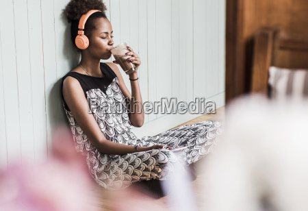 young woman sitting on floor drinking