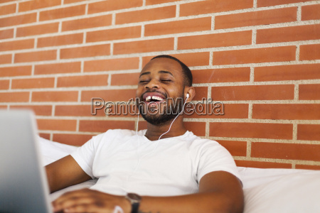 laughing young man with earphones on