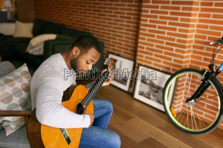 young man at home playing guitar