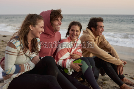 happy friends sitting on the beach