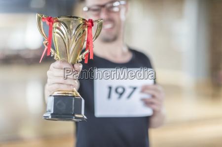 male dance winner holding trophy