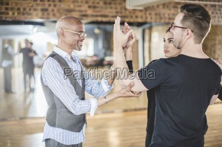 dance instructor leading couple in dance