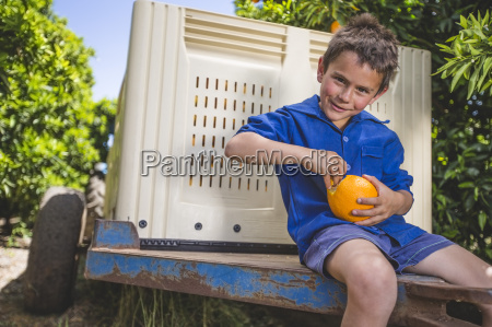 boy sitting on trailer at orange