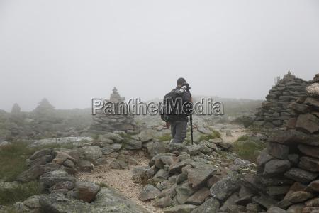 photographer hiking on mount washington during