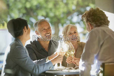 couples toasting white wine glasses at