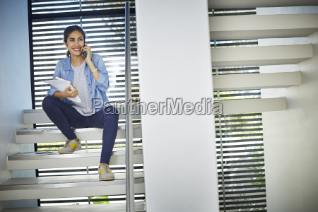 smiling businesswoman with paperwork talking on