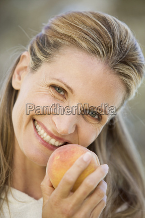 a woman holding a peach