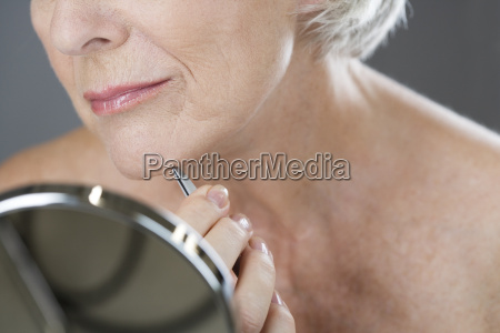 a senior woman plucking hairs from