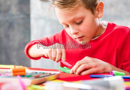 schoolchild cutting plasticine