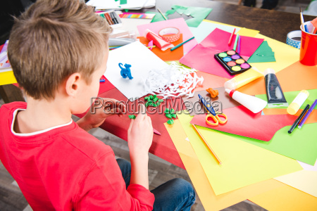 schoolchild making toy from plasticine