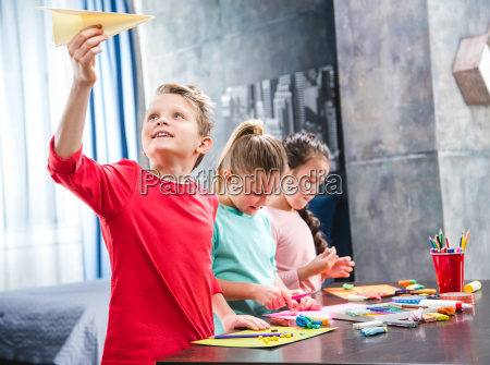 kid playing with paper plane
