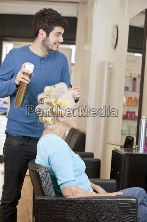 a male hairdresser applying hairspray to