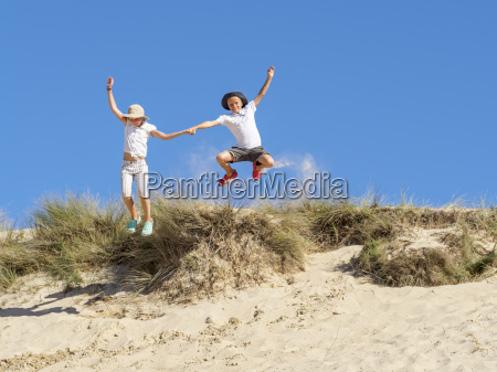 boy and girl jumping from beach