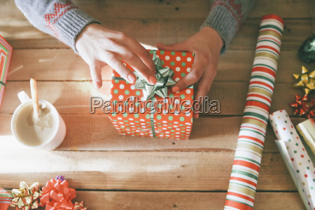 womans hands placing tie on christmas