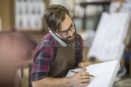 artist in studio with sketch book