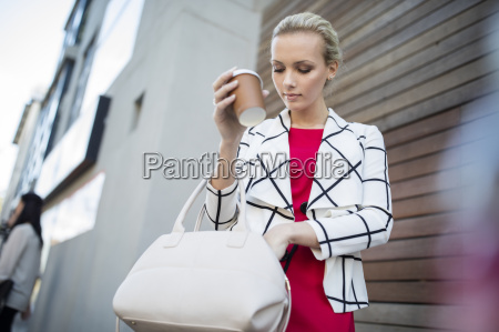 woman with takeaway coffee putting phone