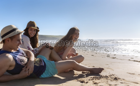 three friends relaxing on the beach