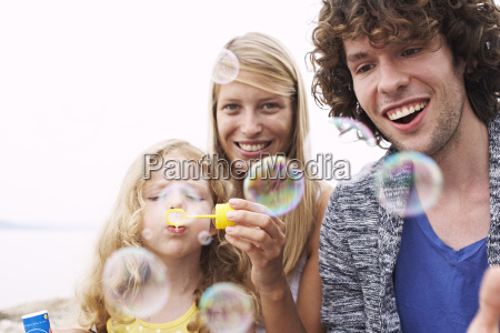 parents with daughter blowing soap bubbles