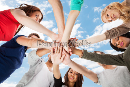 young college students stacking hands