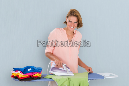 woman ironing clothes using iron
