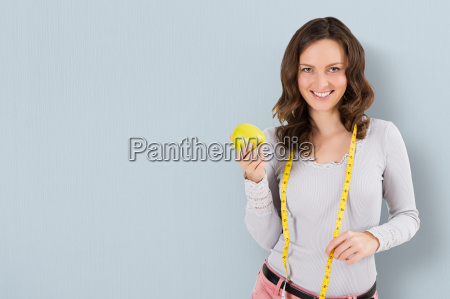 woman with measuring tape and green
