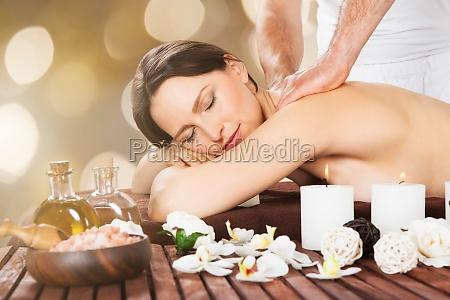 relaxed woman receiving shoulder massage