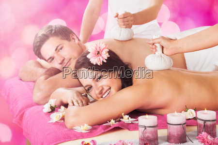 young couple getting massage in spa