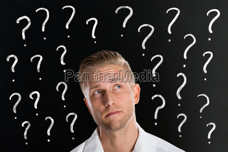 man in front of question marks