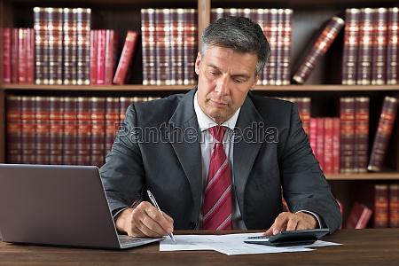 businessman checking bills at desk