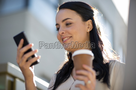smiling woman with takeaway coffee looking