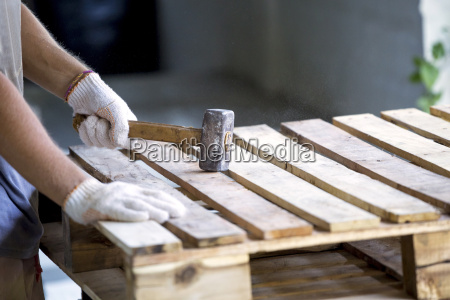 man using hammer on wood