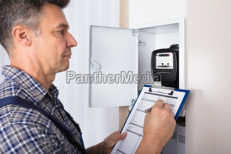 male technician writing reading of meter
