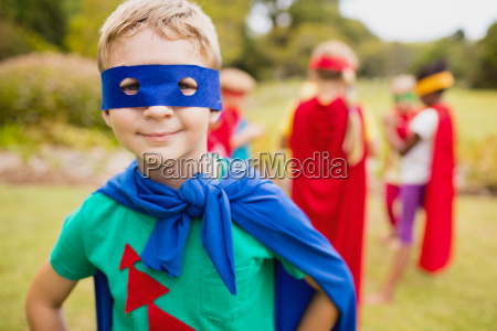 little boy wearing superhero costume posing