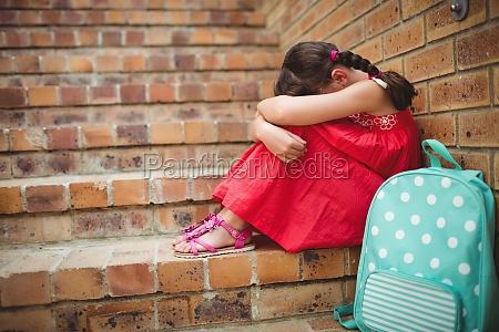 sad schoolgirl with head into her