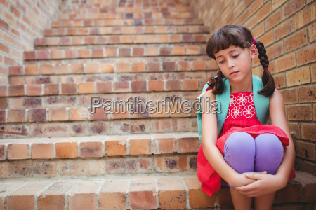 sad schoolgirl siting in stairs