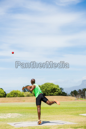 male athlete throwing shot put ball