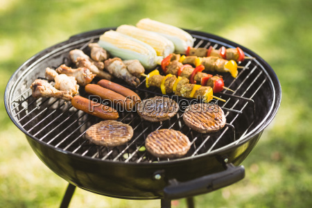 skewers on barbecue grill in garden